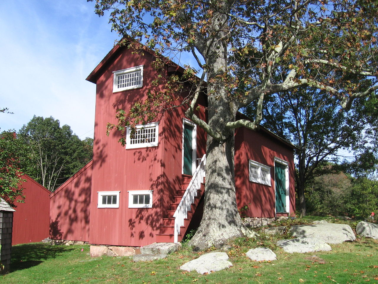 A side shot of Julian Alden Weir's Studio. The three-story building is painted red and has green doors. The windows and outside stair-railings are painted white. Much of the building is obstructed by a large tree. There are stepping stones running through the front yard.
