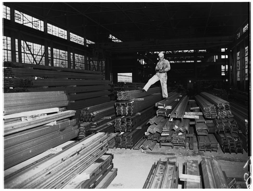 A worker inspects steel beams produced at the mill, 1952 (USC Digital Archives).