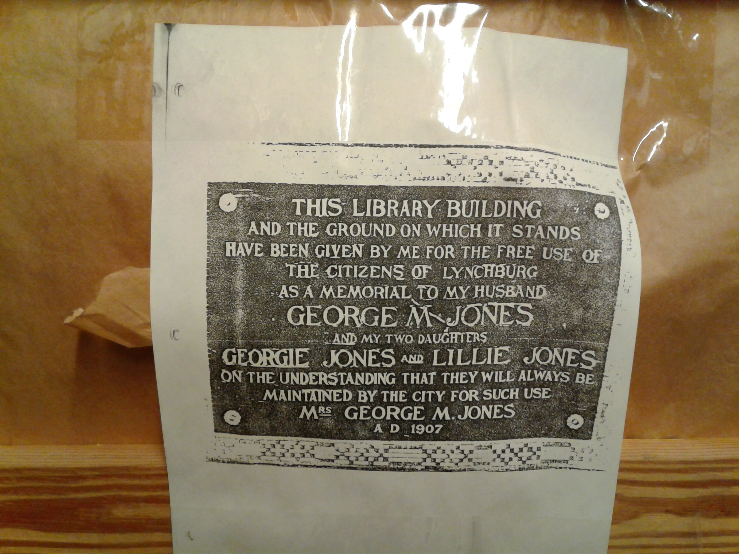 Xerox copy  of plaque where Frances Jones dedicates the Jones Memorial Library to her dead husband George Jones. Original plaque is sealed, has not undergone preservation, only this xerox copy was available.   ~Courtesy Jones Memorial Library