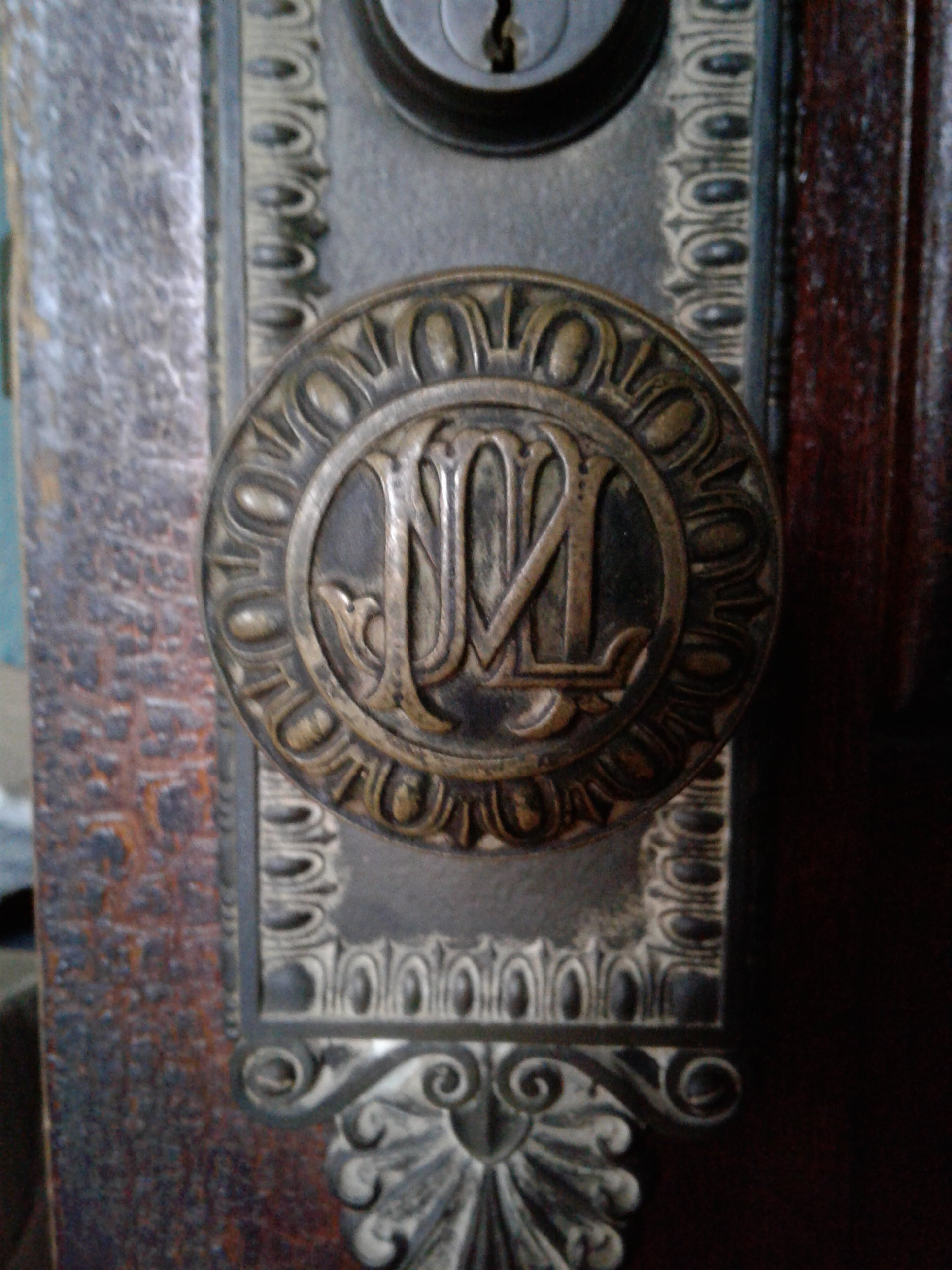 Doorknob in Historic Jones Memorial Library. Initials J.M.L. engraved in each doorknob, egg and dart molding pattern around perimeter of knob and knob plate, anthemion molding pattern along top and bottom of knob plate.
