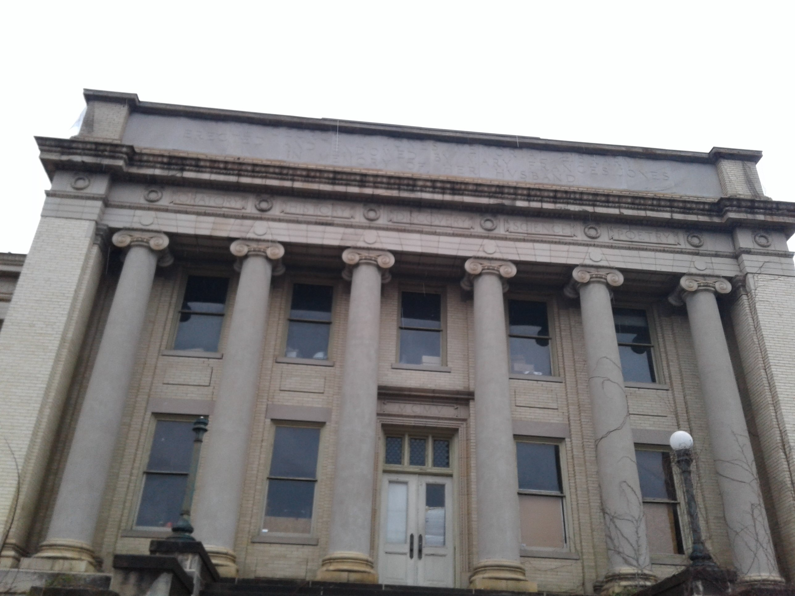 """Front face/entrance of Historic Jones Memorial Library. Top section of building has engraving that states, """"George M. Jones Memorial Library Erected and Endowed by Mary Frances Jones in Memory of Her Husband."""""""