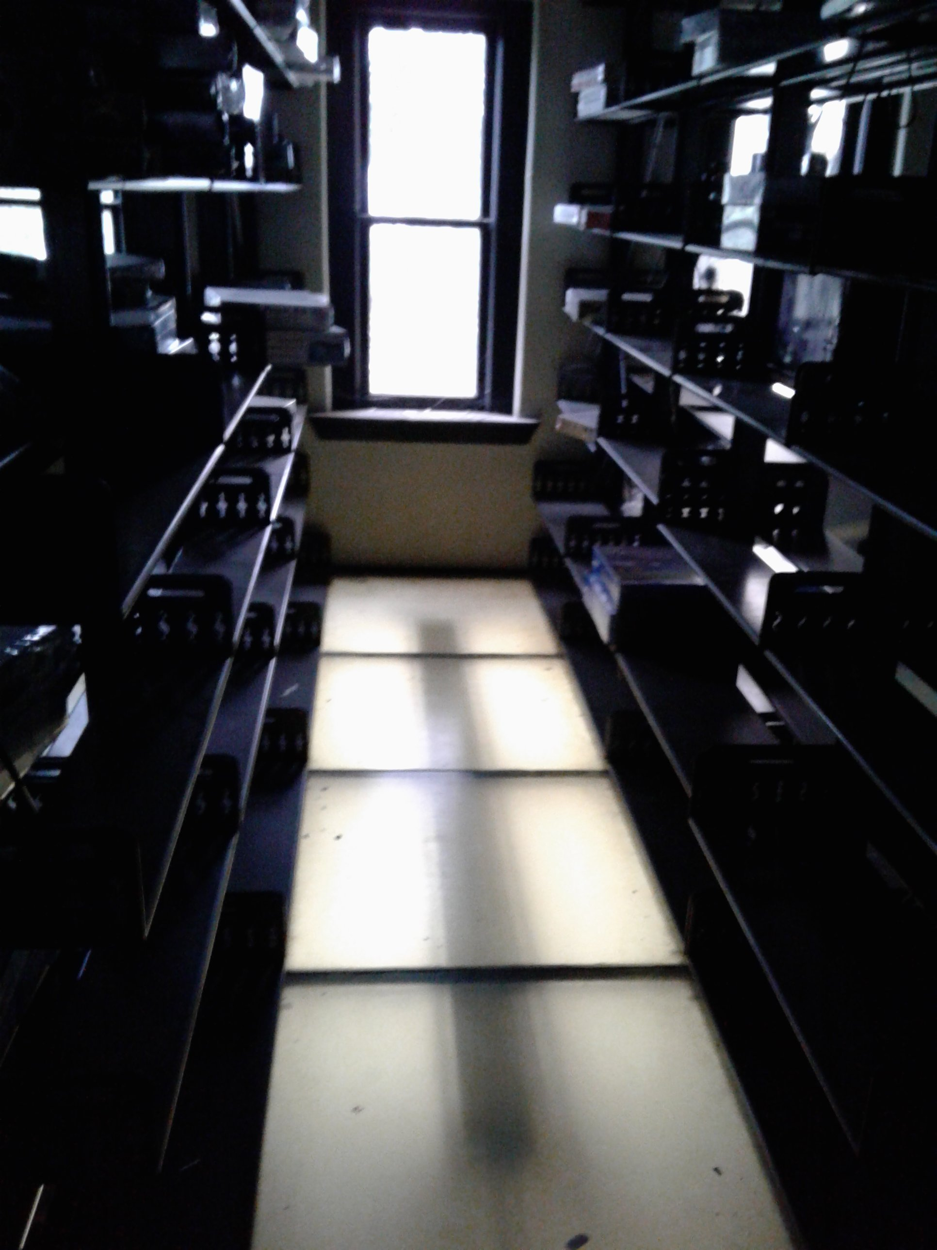 One row of 3-story Library stack with glass floor lighted by ceiling light on floor below in Historic Jones Memorial Library.