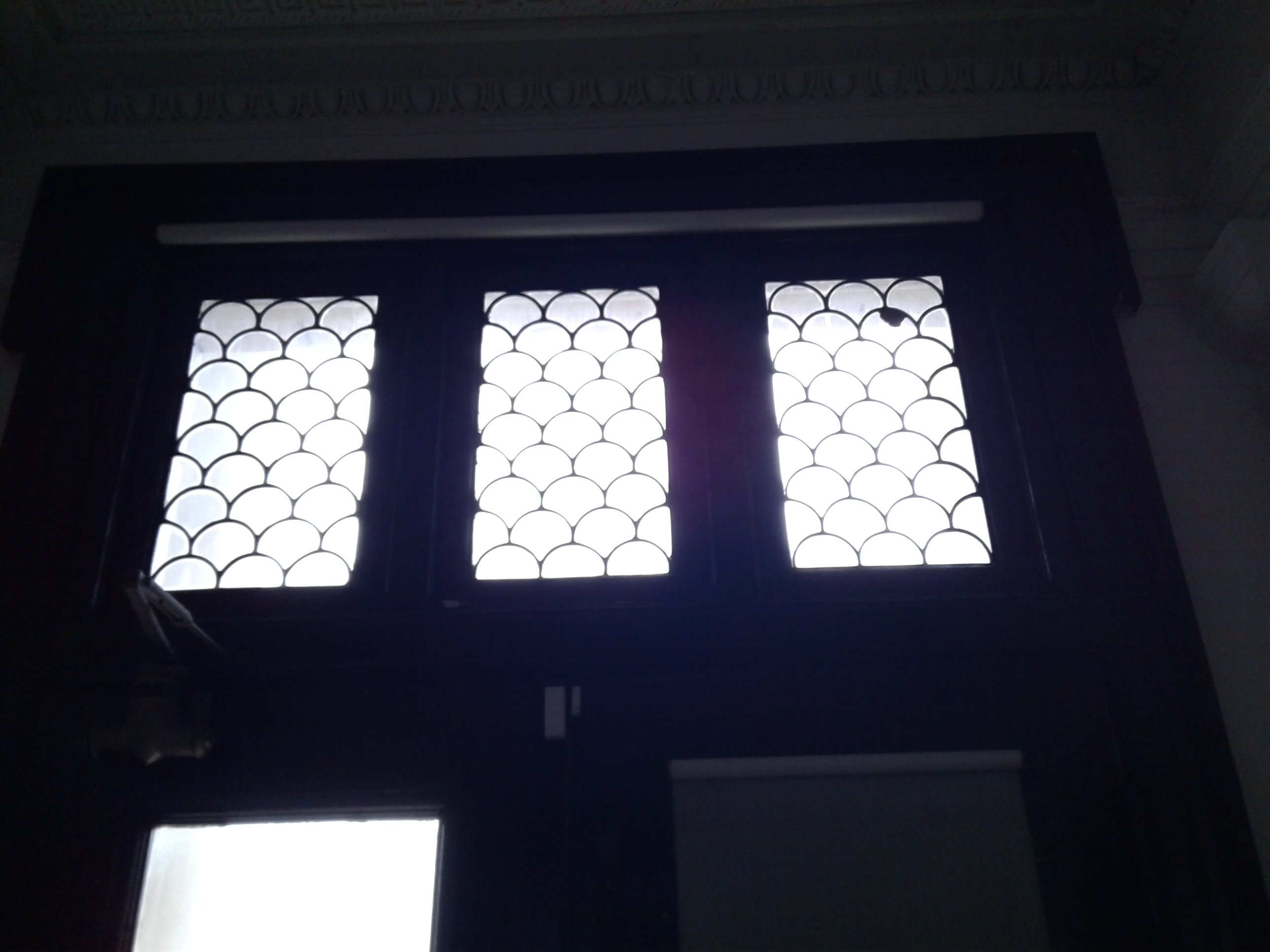 """Leaded glass windows with """"fish-scale"""" pattern above front entrance of Historic Jones Memorial Library."""