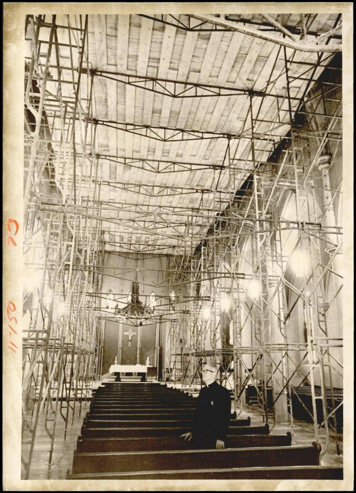 """Photograph used for a story in the Daily Oklahoman newspaper. Caption: """"Rev. Msgr. A.A. Isenbart examines scaffolding in St. Joseph's Old Cathedral which is to undergo a $ 250,000 remodeling job in the next six months."""""""