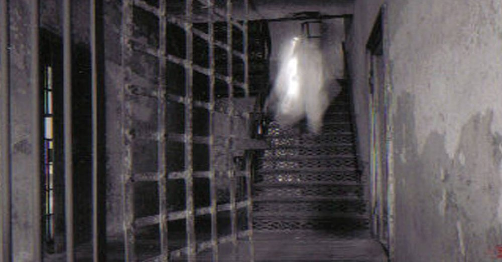 A photo captured of an open rusted cell door by a staircase of what appears to be the ghost of Lavinia Fisher.