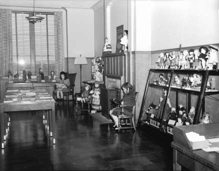 """Two girls reading in the """"Secret Room"""" for children in the Rundel Memorial Library. The George W. Cooper Doll Collection adorns the walls and shelves. (October 25, 1940)"""