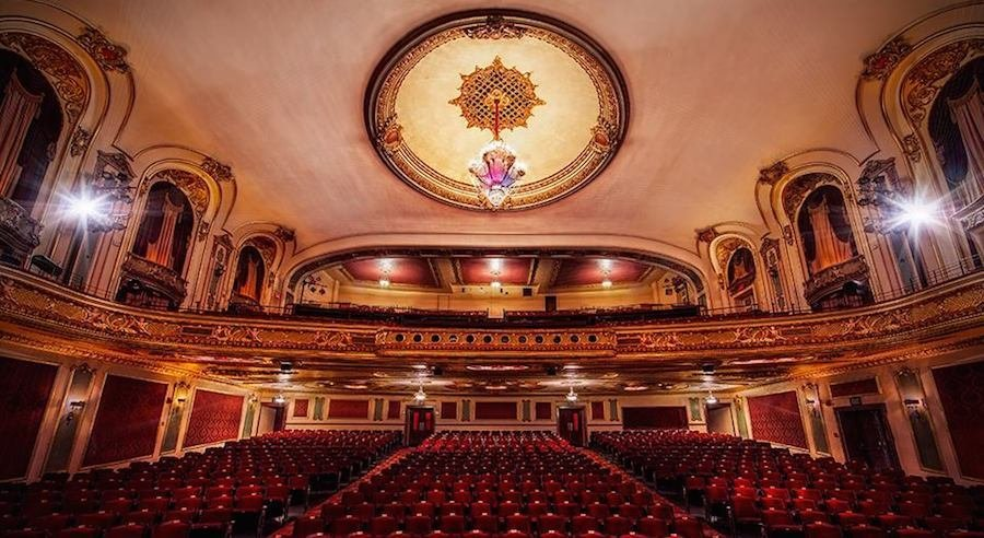 A picture of the concert hall including its grand chandelier and seating.