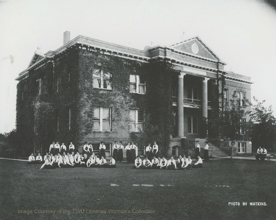 Students in early 1900s relaxing on the lawn in front of Old Main before the addition of wings on either side. The grounds surrounding the school were cultivated by students studying horticulture. (Courtesy TWU Woman's Collection)
