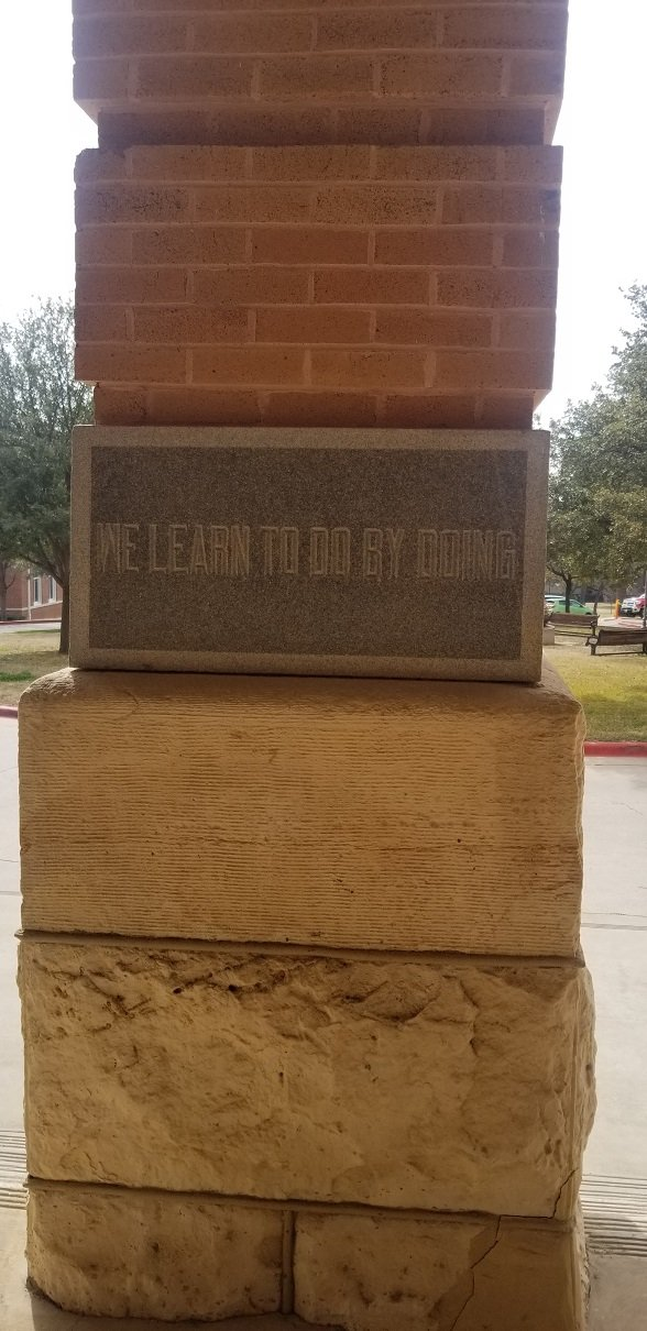 "The cornerstone, laid on January 10, 1903. The motto ""We learn to do by doing"" was suggested by founding member of the Board of Regents, Helen Stoddard."