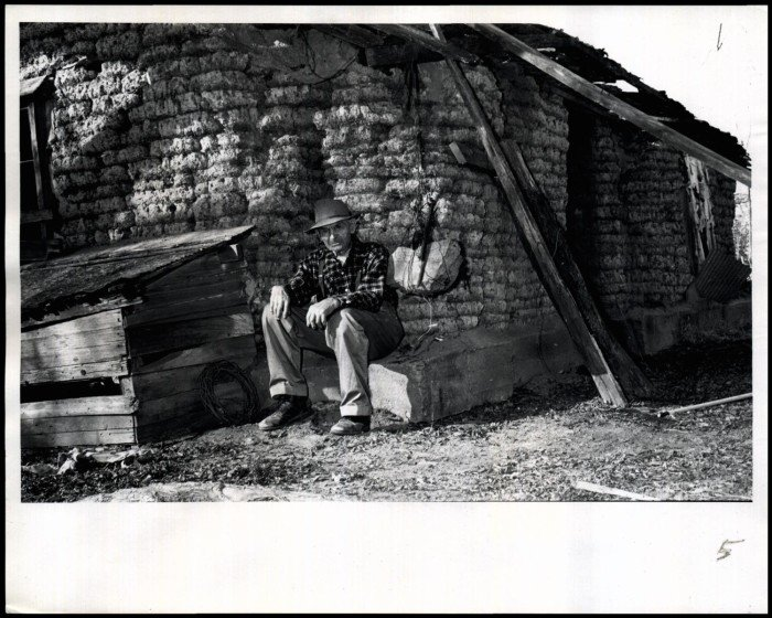 """""""Cherokee Strip Pioneer Marshall McCully suns himself at the corner of the old sod house he built when he settled the land in 1883."""""""