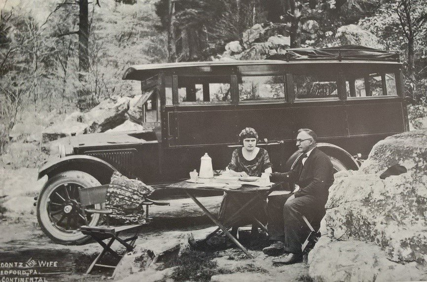 In 1925, Mr. and Mrs. S. H. Koontz share a meal outside of their parked house car, in Bedford. Before the spread of motels and motor courts, travelers would camp in or around their cars (Margolies).