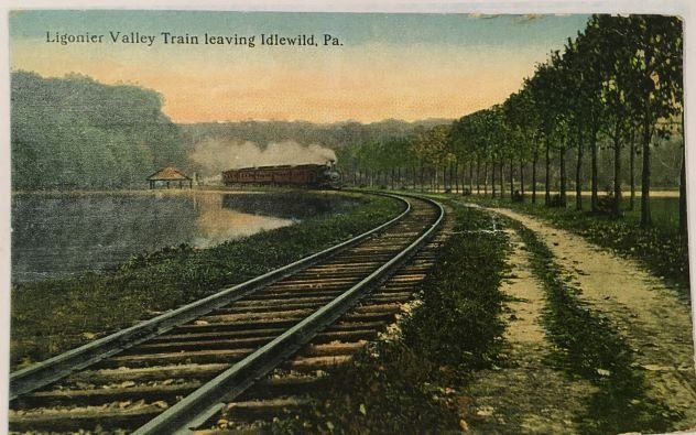 A postcard depicting the Ligonier Valley Rail Road's train/train tracks leaving the Park. Idlewild's presence helped turn the Ligonier Valley RR from being a purely coal transport into a vessel for passenger travel.