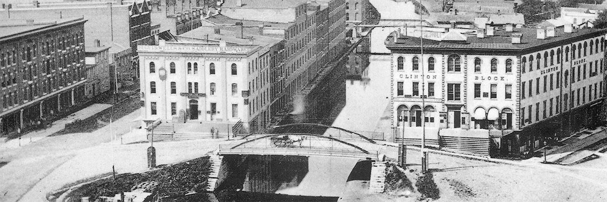 This artist depiction (date unknown) shows the Erie Canal in the center with the Amos Building to its right. The building used to sit along the banks of the Erie Canal, but that is now Erie Blvd.