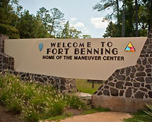 The welcoming sign to Fort Benning in Columbus, Georgia. The sign states how Fort Benning is home of the Maneuver Center of Excellence.