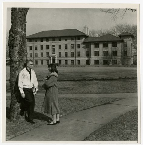 Two students standing beside a tree with Corwin and Larimore halls in the background. Photo courtesy of Elwyn B. Robinson Department of Special Collections, University of North Dakota. UAP28885.