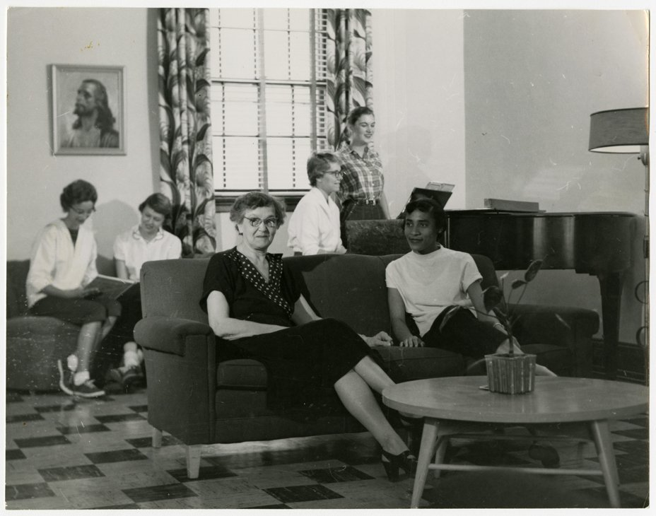 Larimore students enjoying some downtime in the commons area with dormitory house-mother. Photo courtesy of Elwyn B. Robinson Department of Special Collections, University of North Dakota. UAP28928.