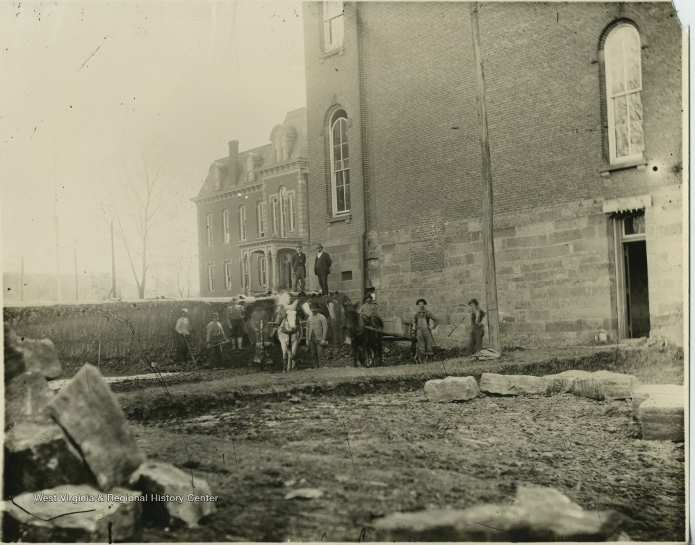Men work to excavate an area for the foundation of the first addition to Woodburn Hall, the north wing. Photo taken ca. 1900