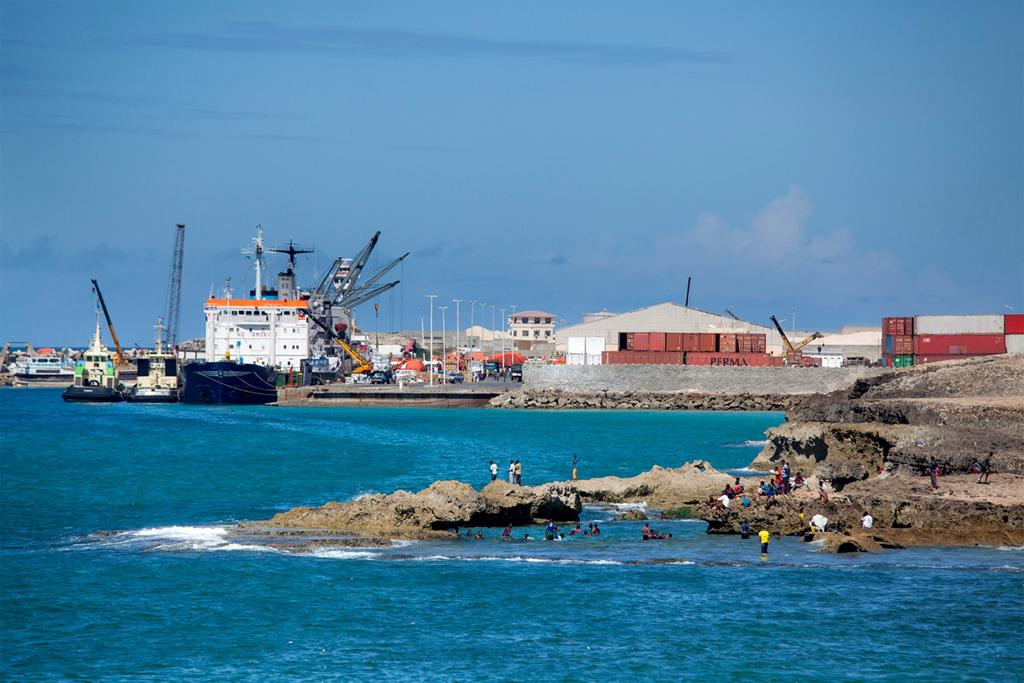 This is a fairly recent photo of the port. People are swimming near the rocks and they are fairly close to a fully functioning port. This photo does a good job displaying both of the uses of the Port. Not only is it utilized for exporting and importi
