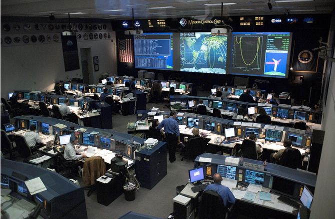 This is an image of a Space Shuttle-era mission control room that featured colored screens as well as a more expanded front screen that allowed for more accurate recording of the spacecraft's functionality.