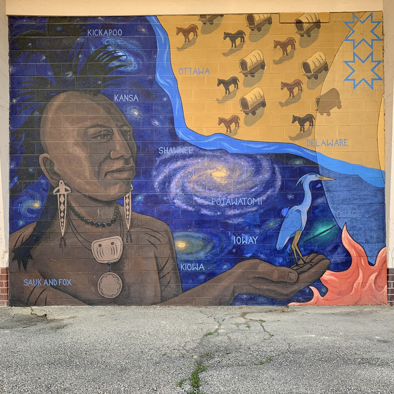 The first panel of the mural that depicts the Native Americans' land being invaded by white settlers.