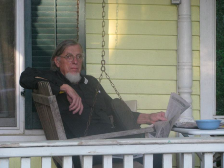 Dr. Orme on his front porch reading the newspaper.