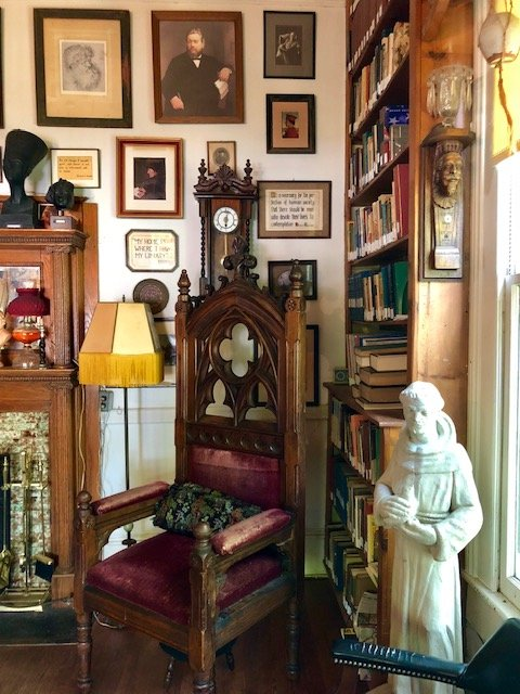 A view of Dr. Orme's library. Pictured also is one of a set of burgundy, velvet chairs originally housed in a church in St. Louis.