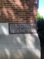 """""""A Memorial To Our Veterans Of ALL WARS""""  Located on East side of front of the building."""