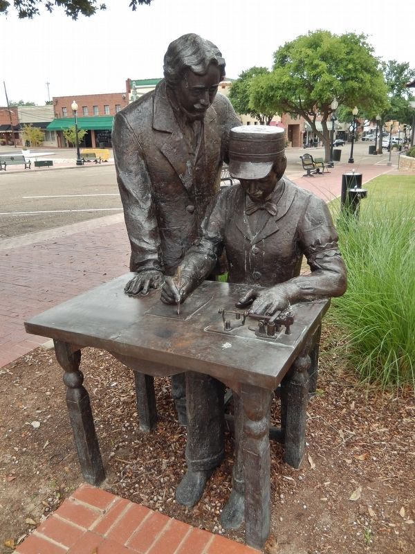 Statue depicting two men receiving a telegram in the first telegraph office established in Marshall.