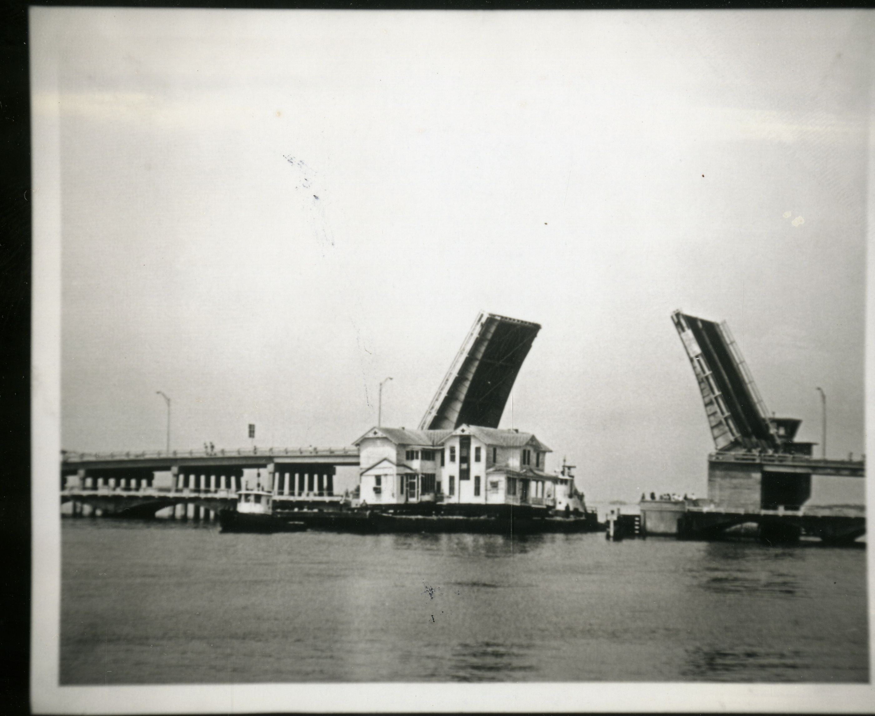 Moving the House of Seven Gables to Heritage Village underneath the Belleair Bridge, 1976.