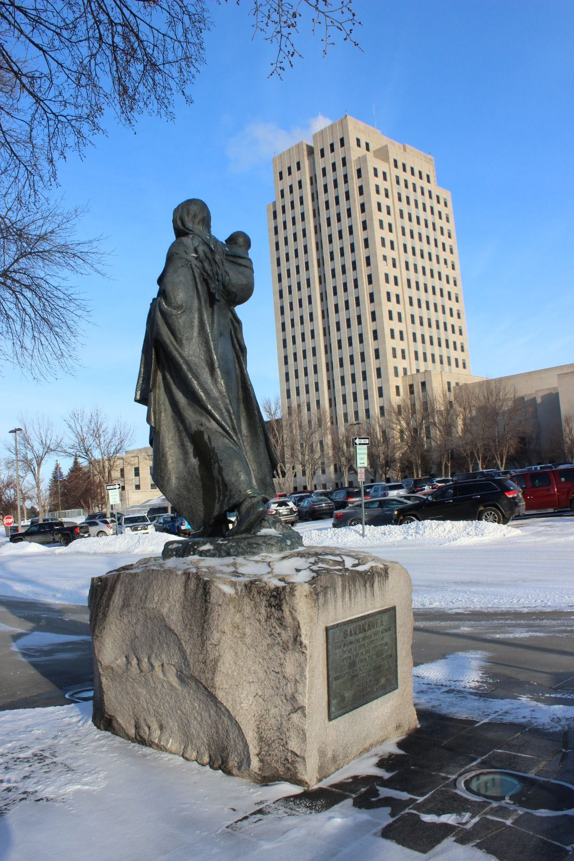 Reverse of Sakakawea statue with North Dakota capitol in background