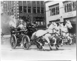 Early photo (c. 1900-1920) showing an example of a horse-drawn fire wagon pulling a steam engine used to pump water