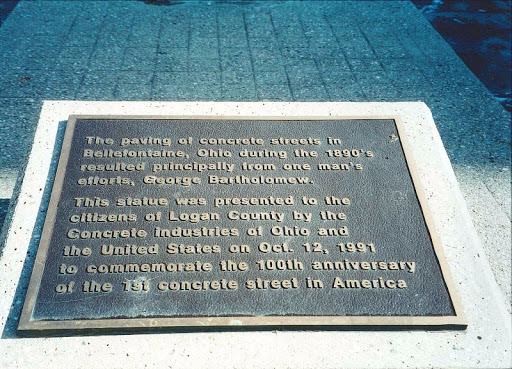 Around the statue of Bartholomew, several plaques tell the history of the oldest concrete street in America.