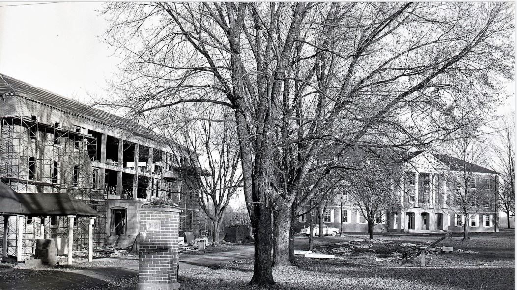 """McCuskey Hall under construction. Notice the """"classic car"""" on the sidewalk and  the old Spring House in the bottom left corner."""
