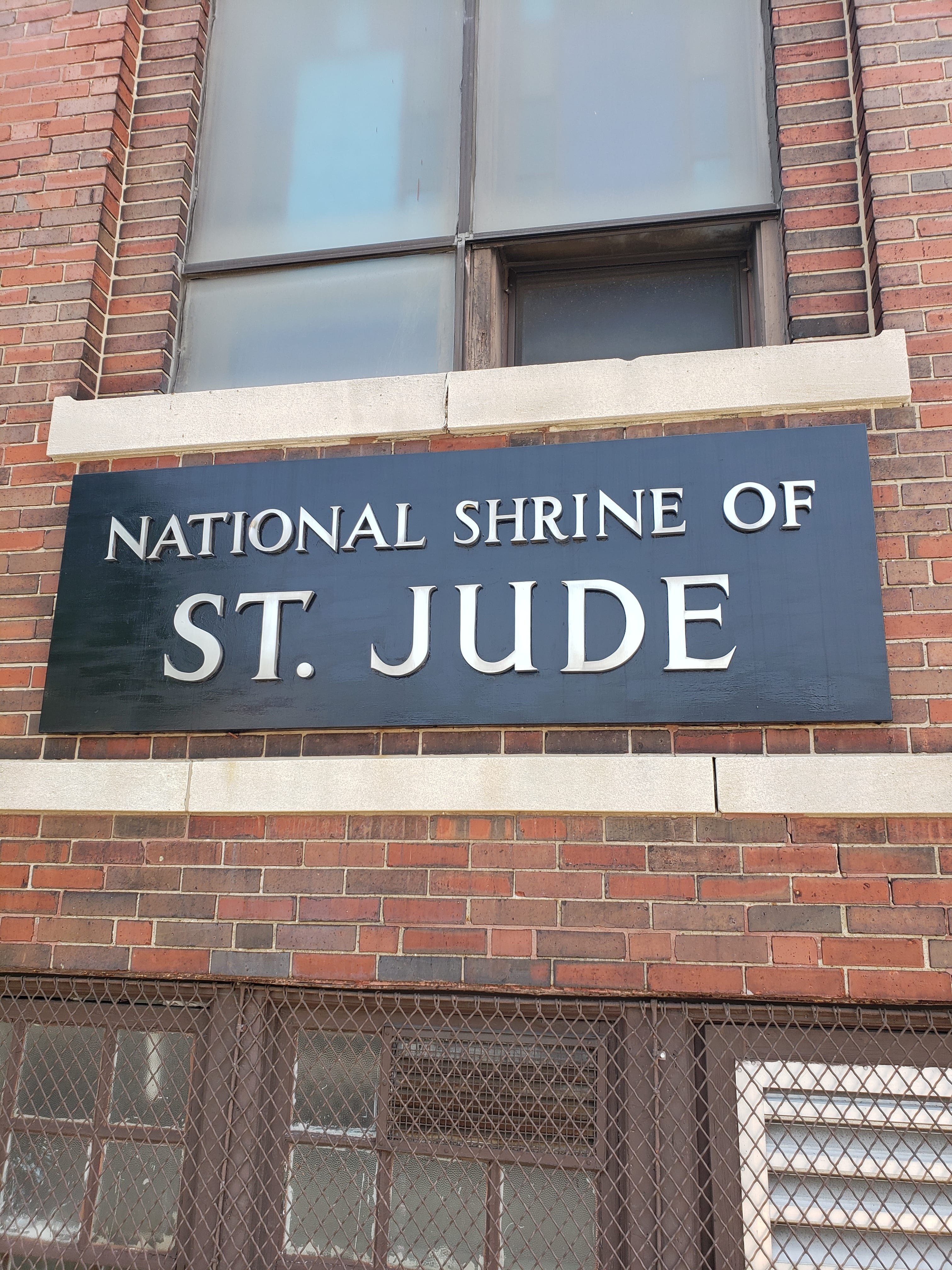 On the left-hand side of the building, a sign indicating the church's historic role as a center of devotion to Saint Jude is prominent.
