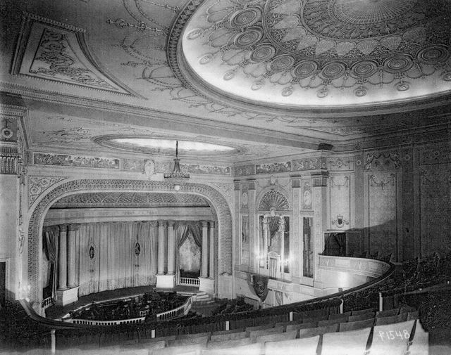 1921 photo with view of Madison Theater with its ornate details, proscenium, main curtain, side stages, and orchestra pit.