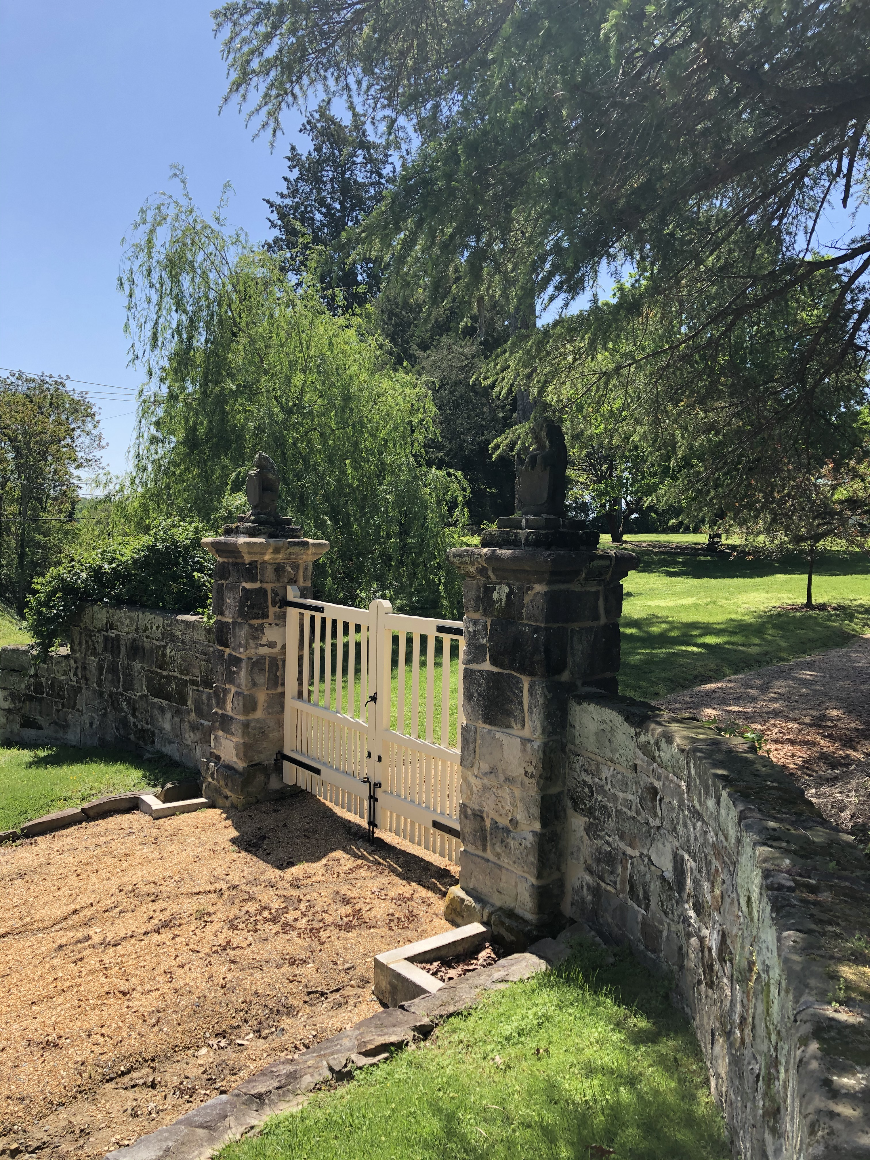 Gate with lion-topped posts and stone wall