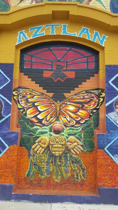The old doorway that once led visitors inside Casa Aztlan is repainted with symbols from the original mural, including the black Aztec eagle (Credits: Elena Andrews, 2019)