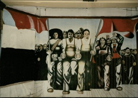 A mural that once covered an interior wall at Casa Aztlan, painted by Marcos Raya and depicting community members marching under the red flag of the Huelga (strike) (Credits: Dr. Margaret LaWare, 1991)