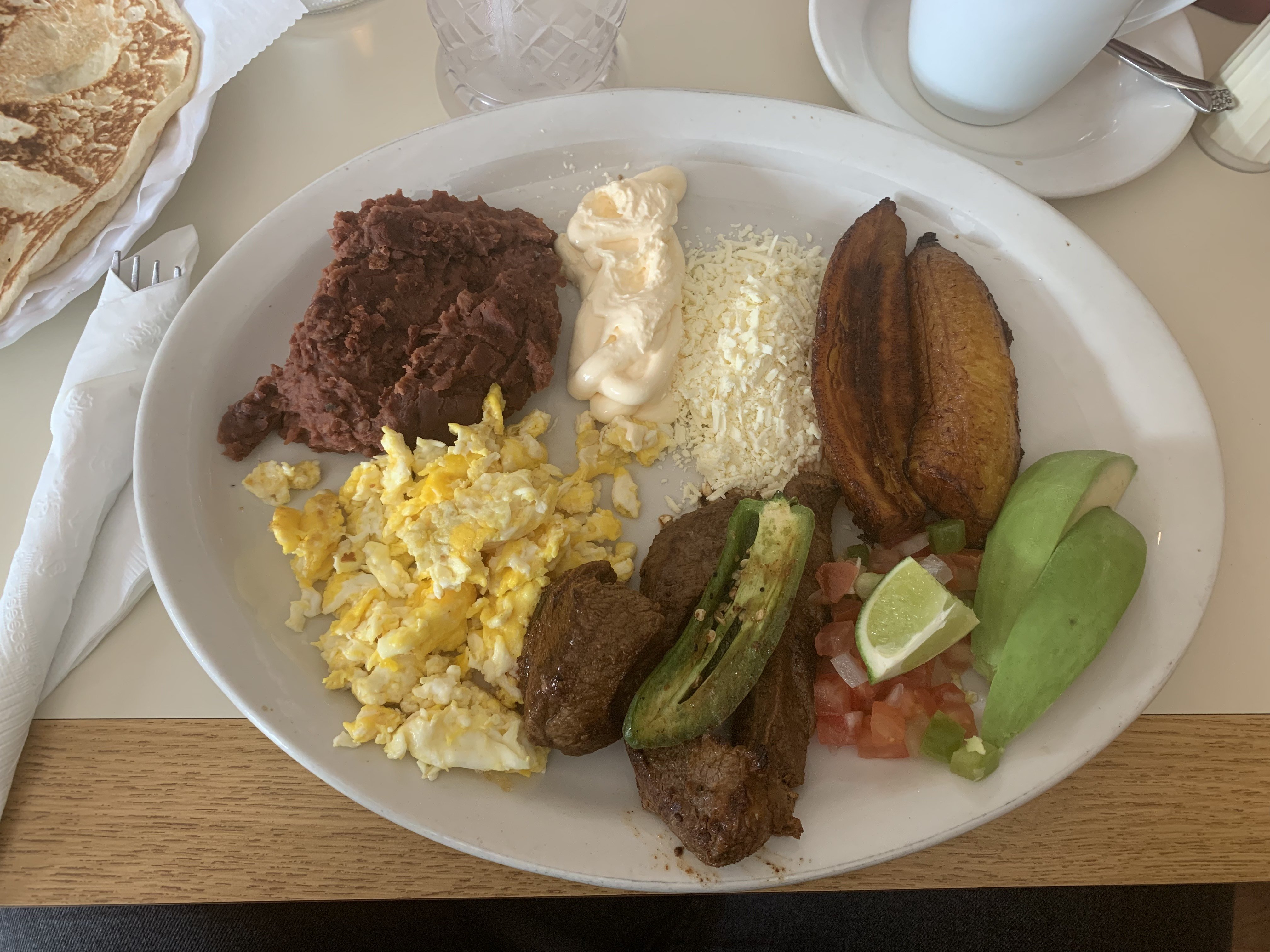 The desayuno tipico features meat, eggs, beans, plantains, pico de gallo, cheese, and avocado. It is served with a tortilla.
