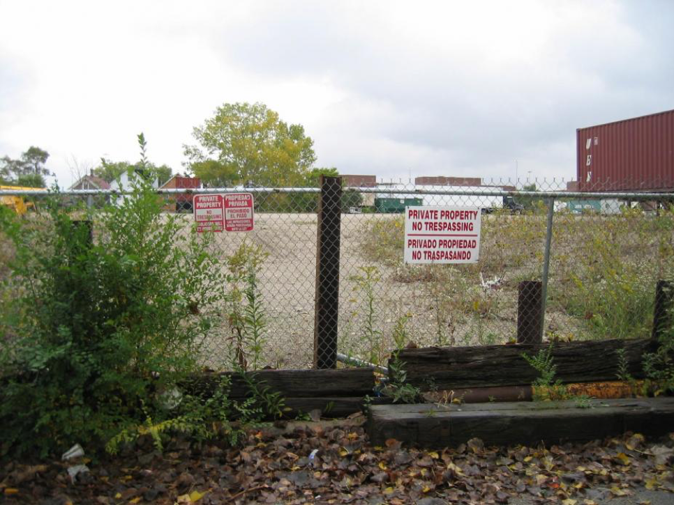 This image shows the state of the Celotex site prior to cleanup. Plastered with private property signs, the chain link fence kept out the community and its public interests. Its reclamation created a space taken by the community for the community.