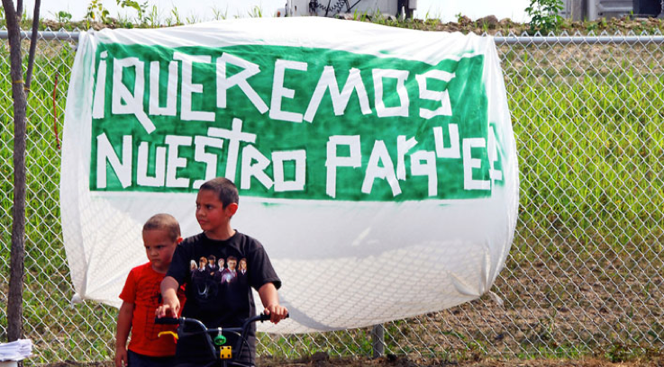 """While the white sheet could have been a flag of surrender, it was marred with green paint, the color of hope. Activists hung this sign as a part of the fight for the realization of this hope: that there would be a park to call """"ours."""""""
