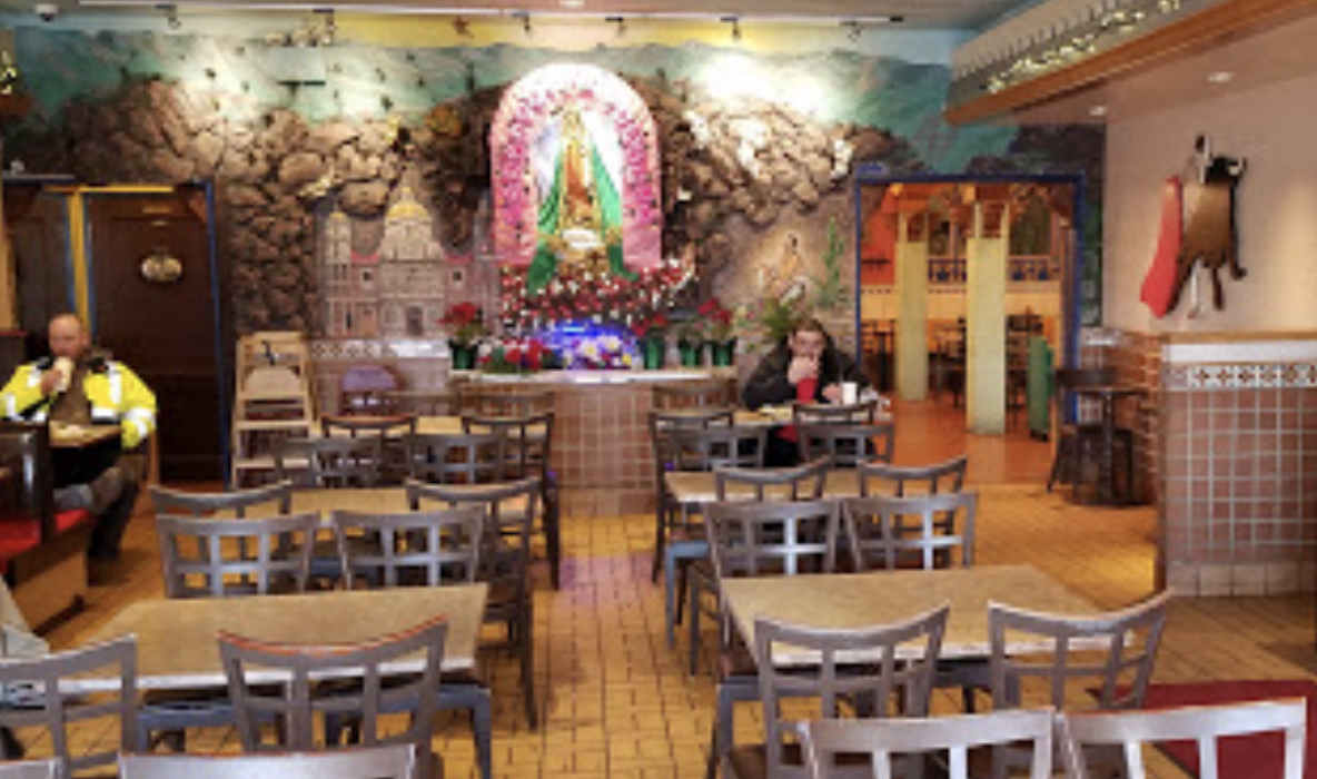 The inside of the Taqueria El Milagro. A Virgen de Guadalupe stands wall to wall in the back.