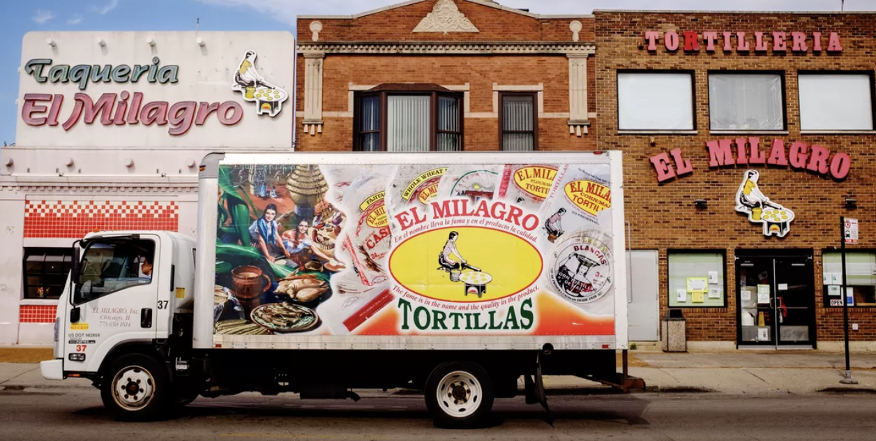 El Milagro truck parked in front of the building. The truck is responsible for delivering tortillas to stores every day.