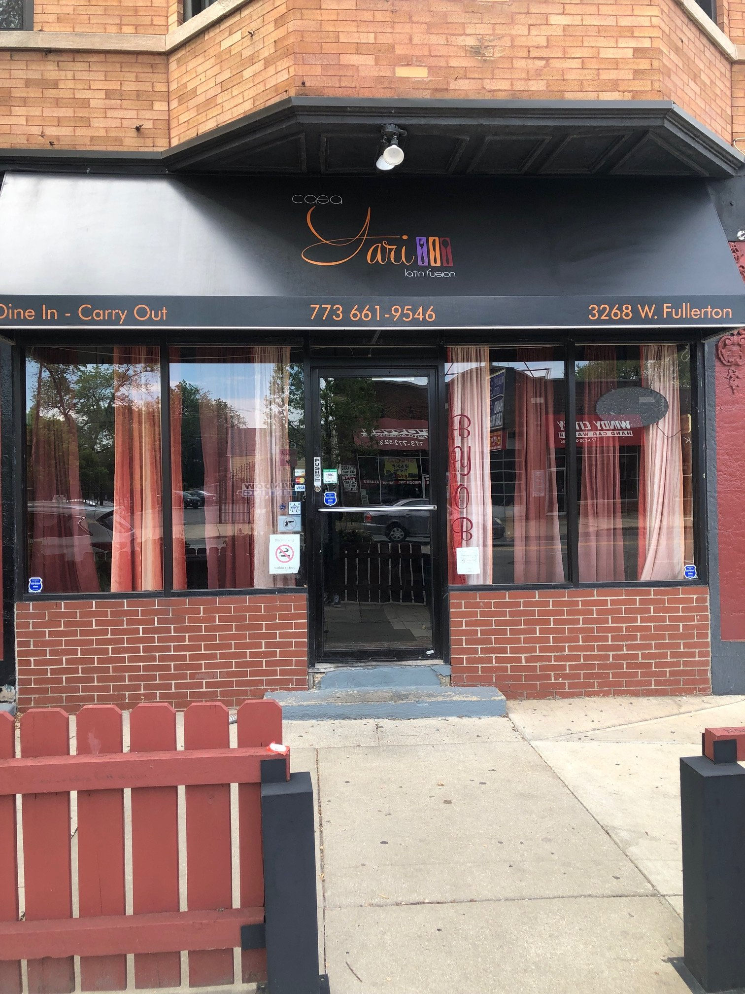 The front entrance of Casa Yari at 3268 W Fullerton Avenue, Chicago, IL 60647. The vibrant red entry invites customers in for dine in or carry out options. Noted on the windows is the BYOB option for the restaurant.