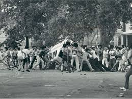 https://chicagoganghistory.com/division-street-riots/ This picture is from the 1966 Division Street Riot. The image shows rioters flipping a car over. Over the course of the three day riot many cars were flipped and many buildings were destroyed. Es