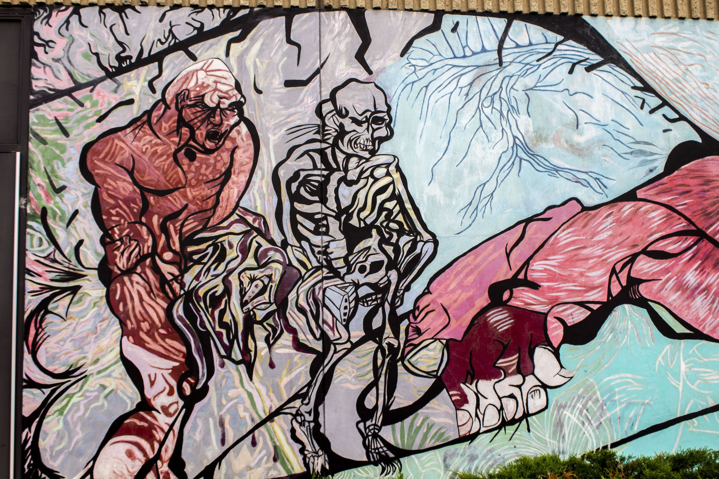Here is another part of the mural that features a skeletal and flaming red figure intertwined. The skeleton on the right is leading the flaming figure who seems so be forcibly holding a concealed gun. These characters represent gangbangers and the st