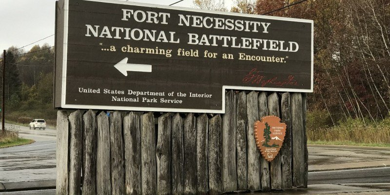 "This is the welcome sign when entering Fort Necessity, what is comical about this sign is the fact that it uses Washington's quote when he said that it would be a ""charming field for an encounter."""
