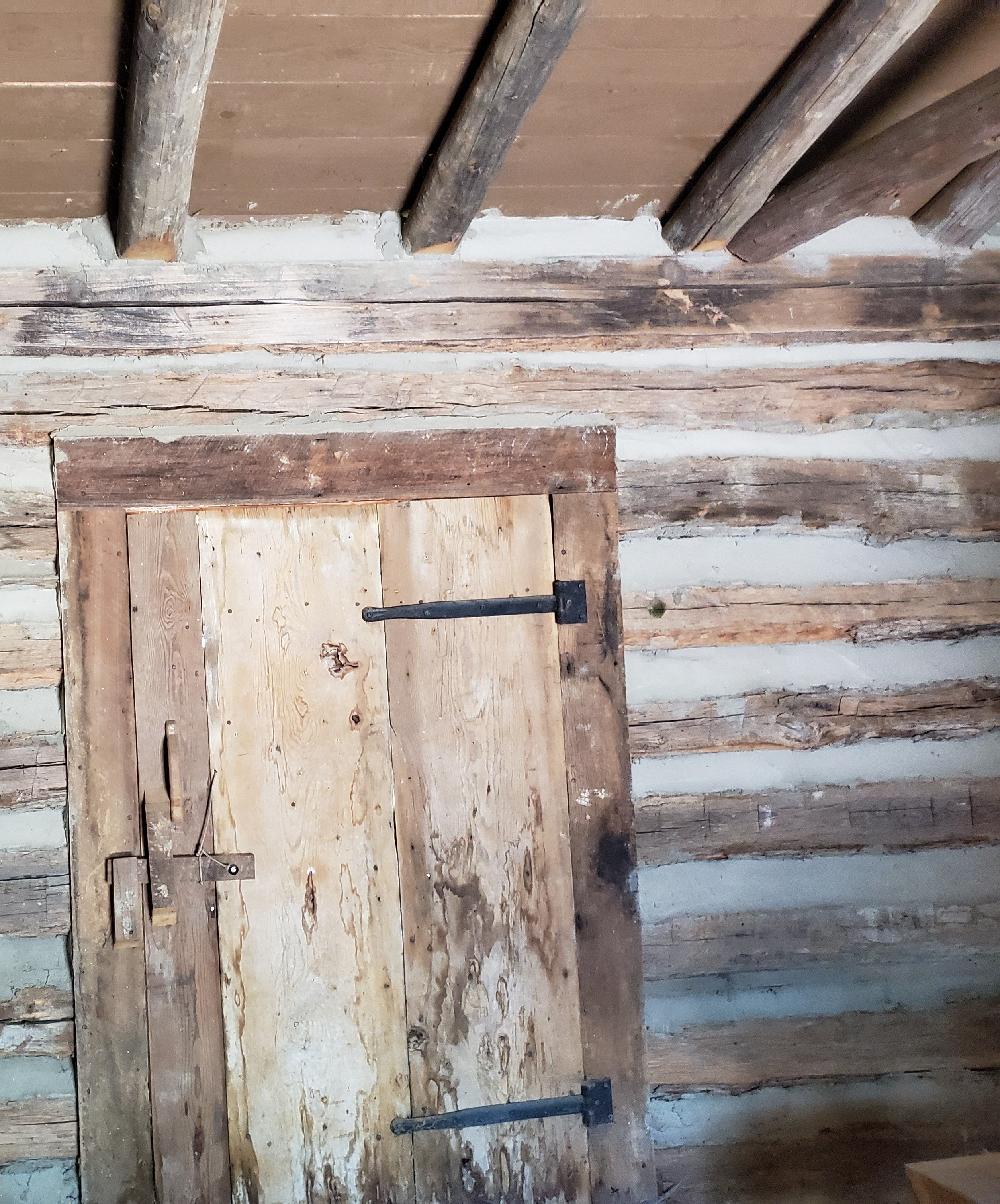 This is a view of the schoolhouse door from the inside. Windows were open holes cut into the logs to provide light and ventilation during warm weather but there was no glass or closures to keep the outside elements out.
