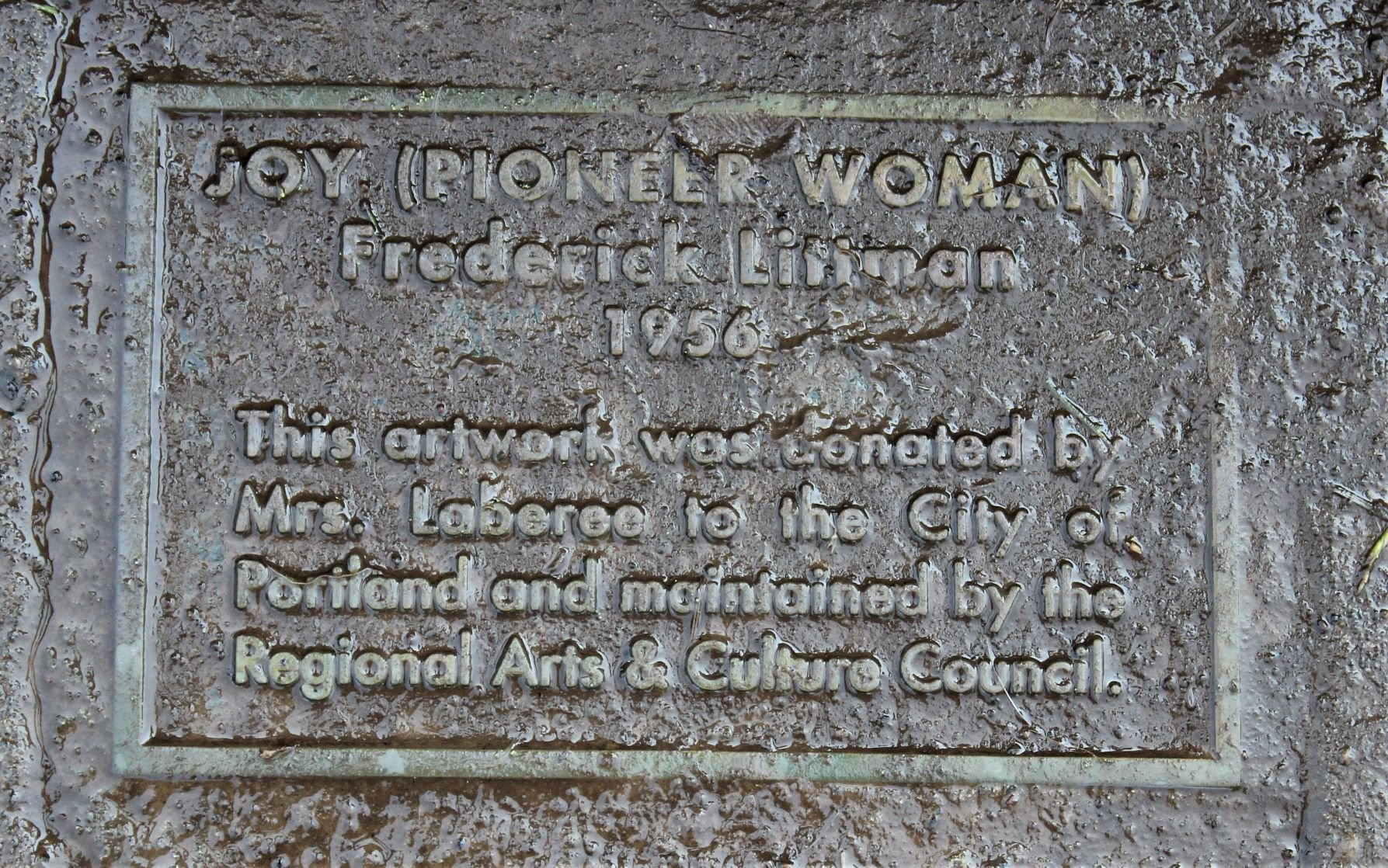 Joy (Pioneer Woman) plaque at base of fountain. Photo by Cynthia Prescott.