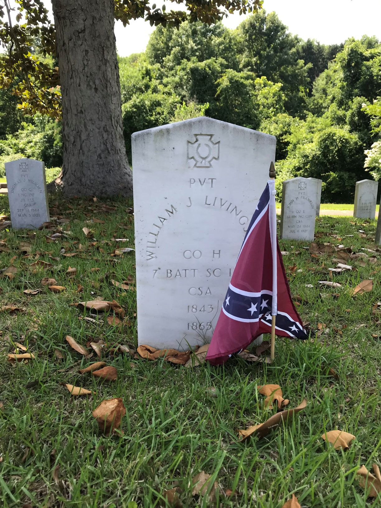 A gravestone decorated with a Stars and Bars flag.